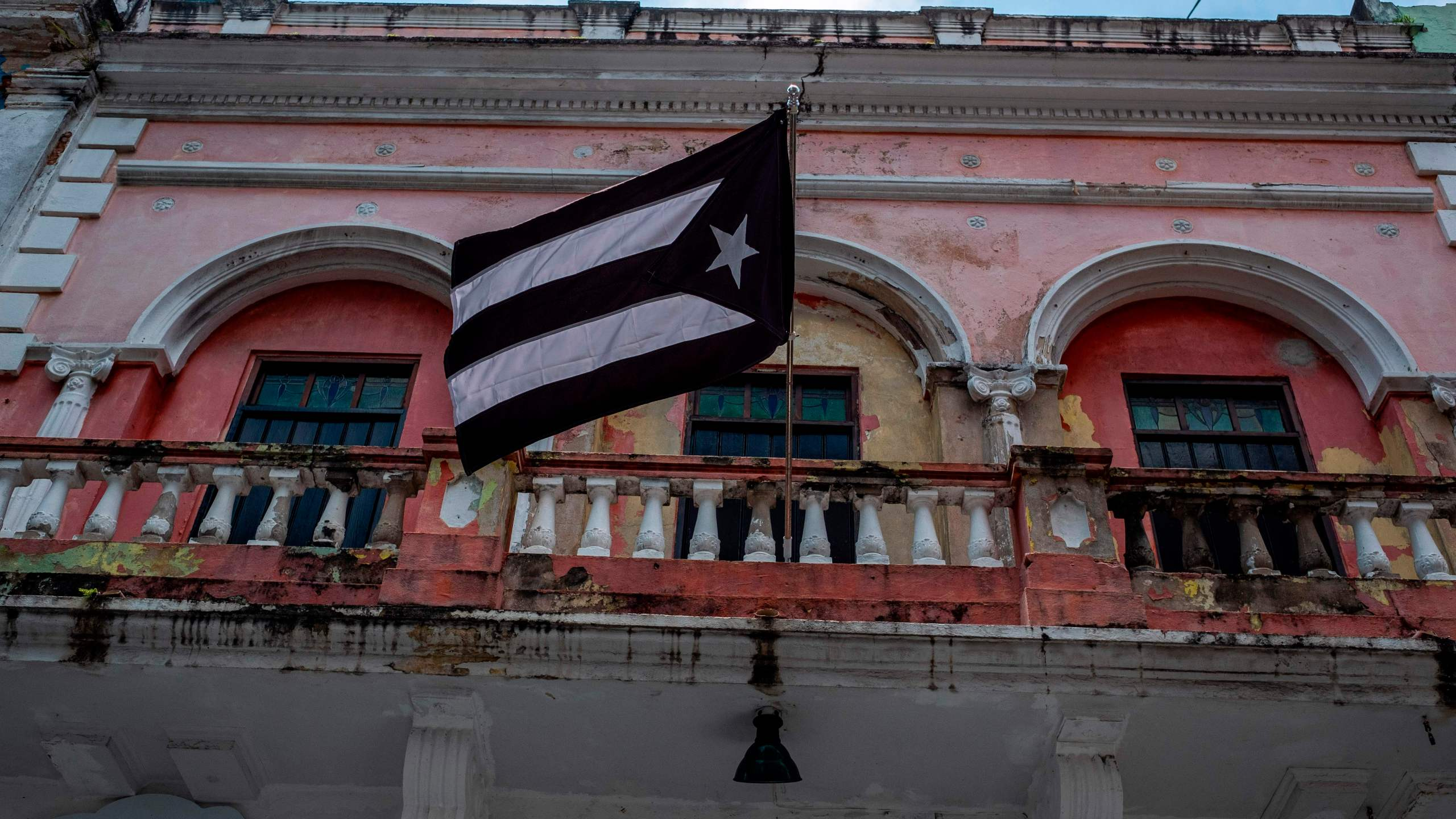A black and white Puerto Rican National flag hangs from a balcony in Old San Juan, Puerto Rico on April 7, 2020. (RICARDO ARDUENGO/AFP via Getty Images)