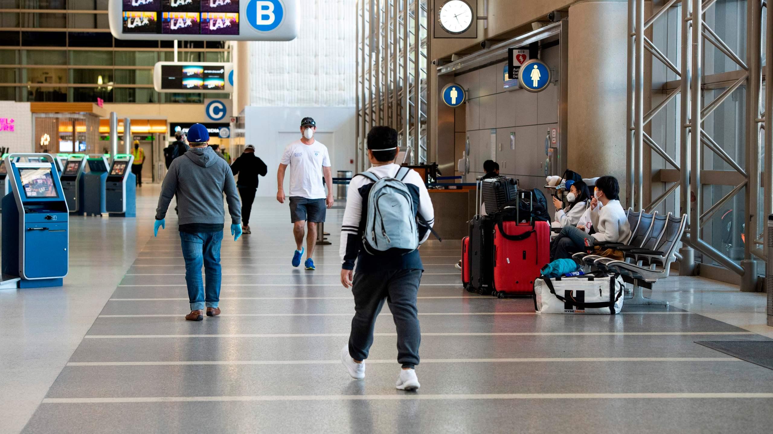 People wearing masks walk inside Tom Bradley Terminal at Los Angeles International Airport on April 16, 2020. (VALERIE MACON/AFP via Getty Images)