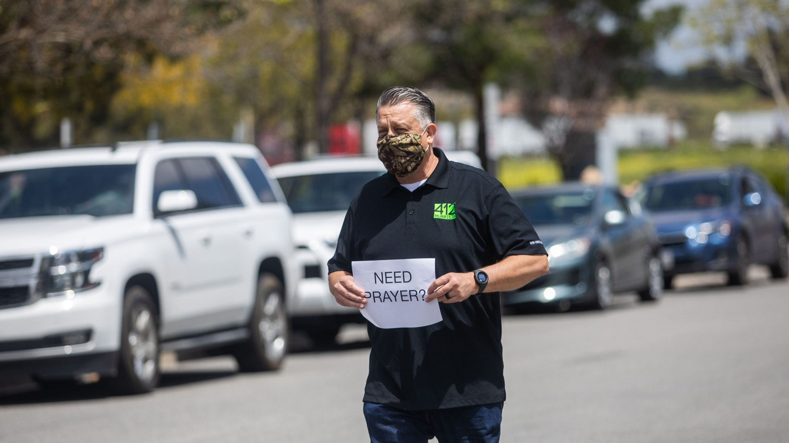 Simon Cooper offers prayers to people who attended an online Sunday Service inside their cars at the Christian '412 Church Murrieta' parking lot on April 19, 2020, in Murrieta, California. (APU GOMES/AFP via Getty Images)