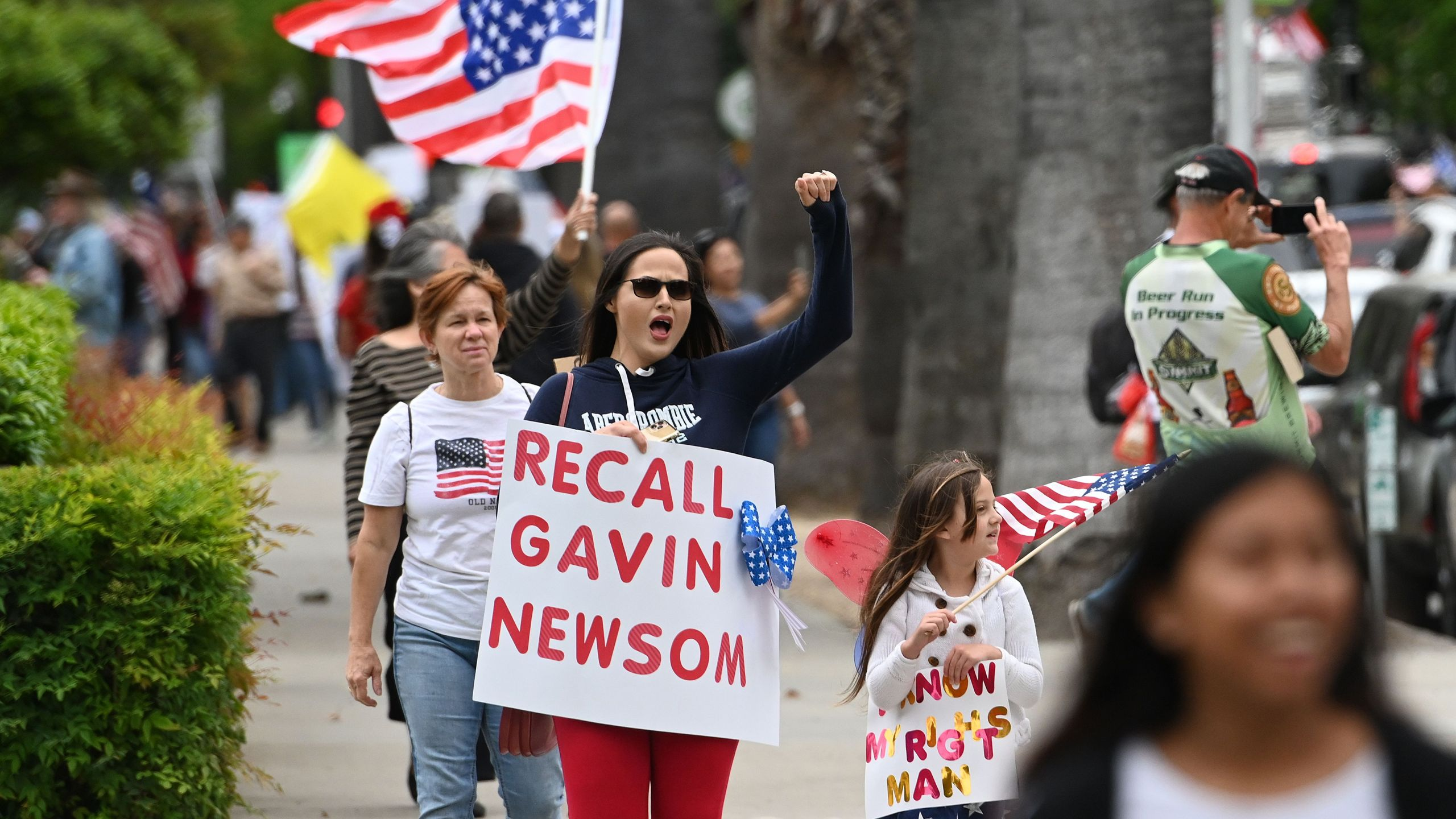 A woman shouts with a sign calling for the removal of California Gov. Gavin Newsom as hundreds of people gather to protest the lockdown in spite of shelter-in-place rules still being in effect at California's state capitol building in Sacramento, California on April 20, 2020. (JOSH EDELSON/AFP via Getty Images)