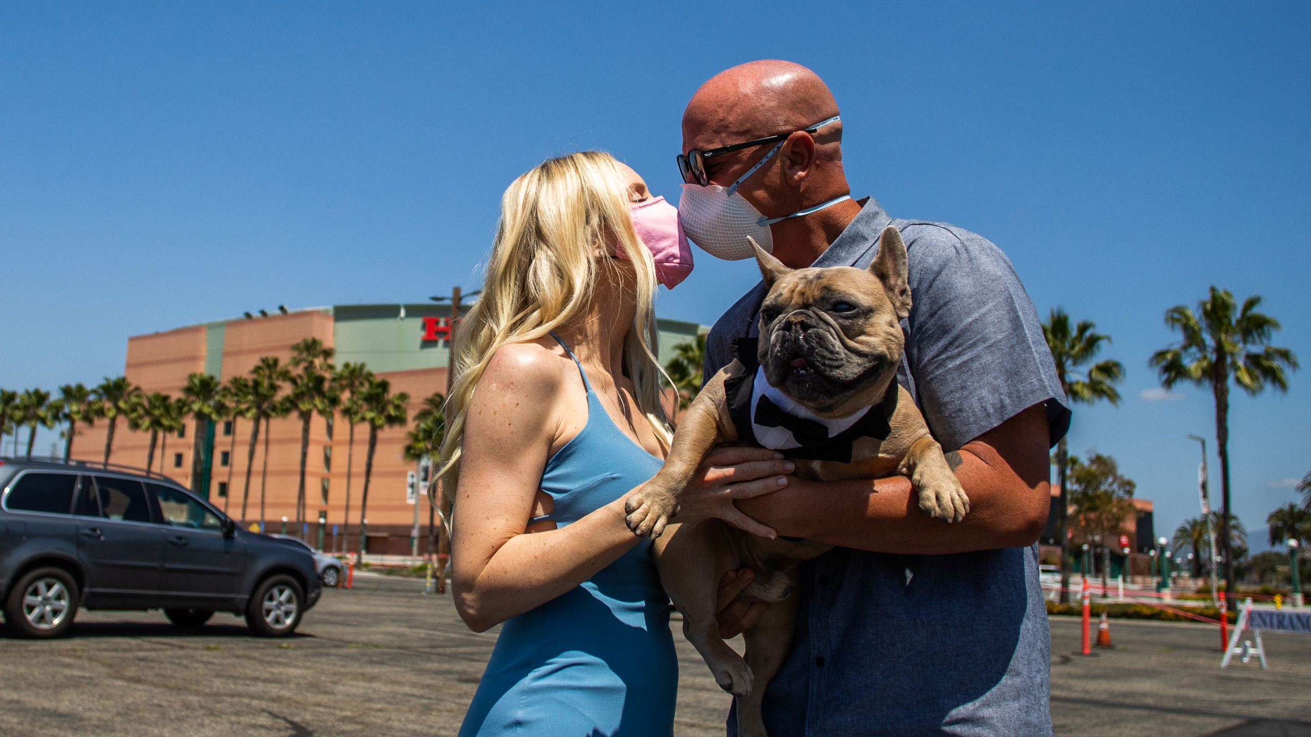 A couple kisses wearing face masks and holding their dog after their wedding ceremony officiated by a clerk recorder at the Honda Center parking lot on April 21, 2020, in Anaheim, California. (APU GOMES/AFP via Getty Images)