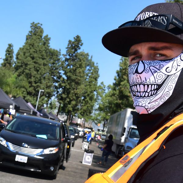 A masked volunteer looks on as vehicles arrive at a Los Angeles Regional Food Bank drive-thru giveaway in Pico Rivera on April 28, 2020. (Credit: Frederic J. Brown / AFP / Getty Images)