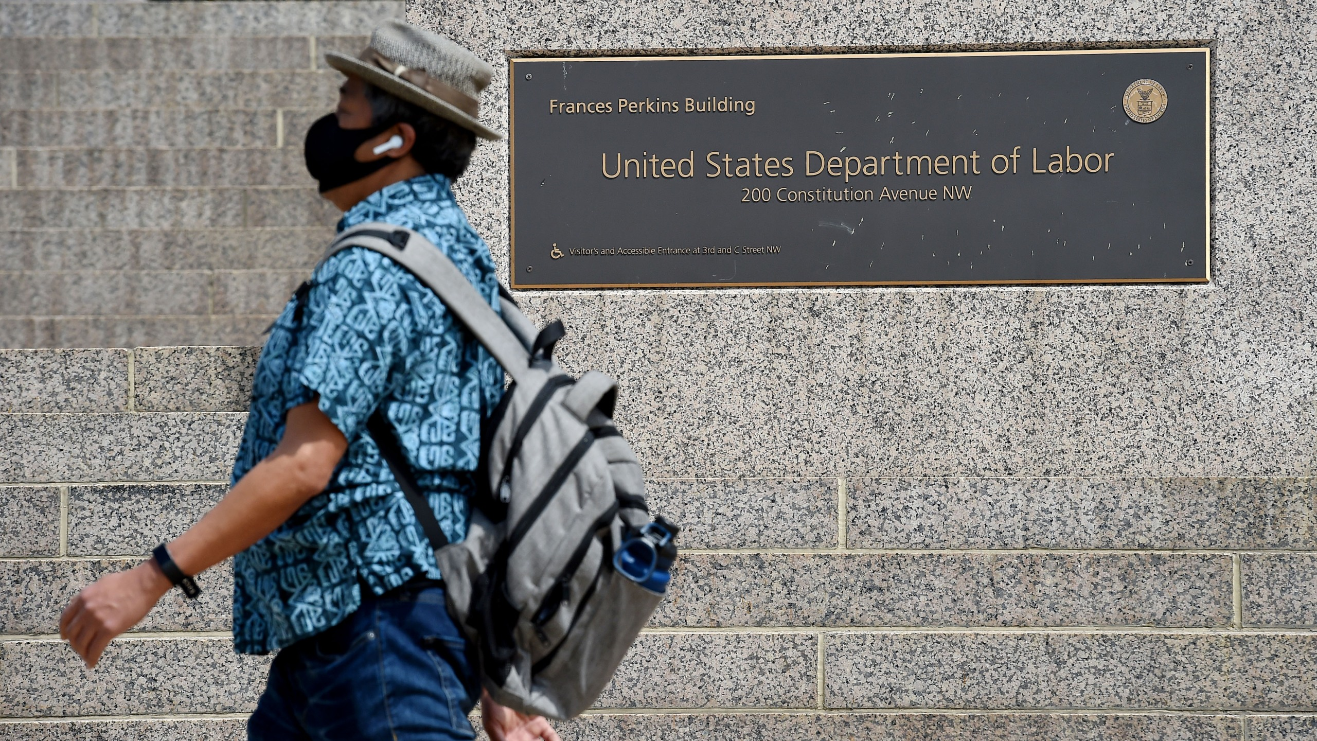A man wearing a face mask walks past a sign in front of the US Department of Labor amid the coronavirus pandemic on April 29, 2020, in Washington, DC. (OLIVIER DOULIERY/AFP via Getty Images)