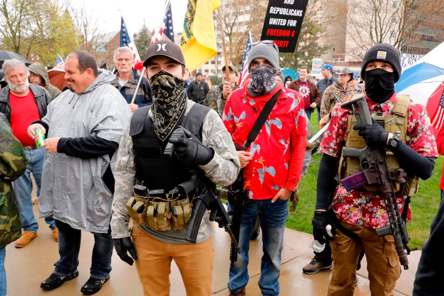 """Armed protesters provide security as demonstrators take part in an """"American Patriot Rally,"""" organized on April 30, 2020, by Michigan United for Liberty on the steps of the Michigan State Capitol in Lansing, demanding the reopening of businesses. (JEFF KOWALSKY/AFP via Getty Images)"""
