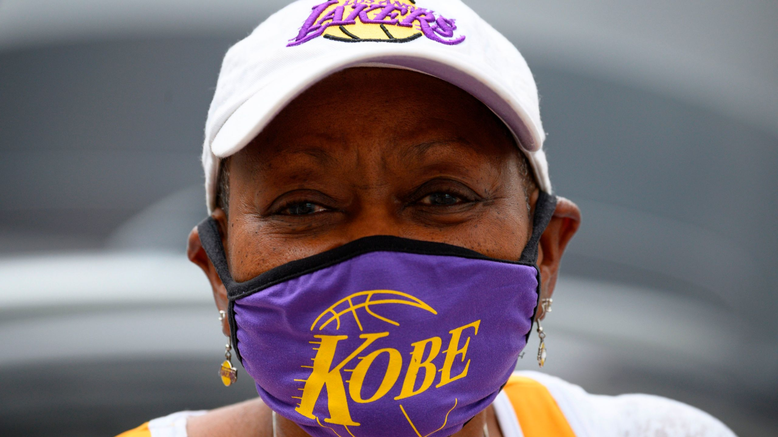 Carrie Harris Allen sells face masks, including the Kobe Bryant style she is wearing, in downtown Los Angeles on April 30, 2020. (Credit: Robyn Beck / AFP / Getty Images)