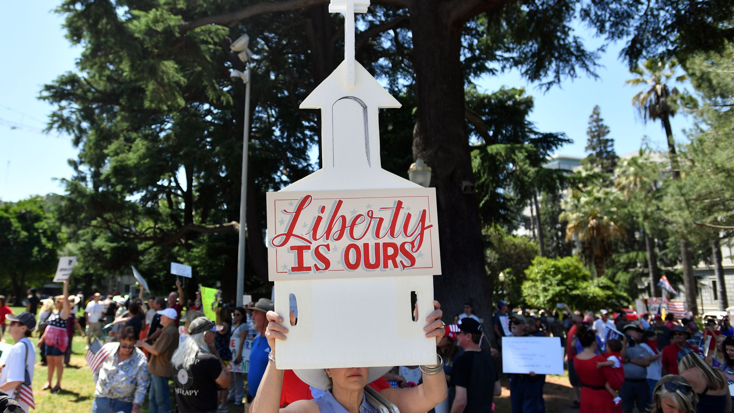 A woman holds up a sign depicting a church as hundreds of people gather to protest the stay-at-home orders outside the state capitol building in Sacramento on May 1, 2020. (JOSH EDELSON/AFP via Getty Images)