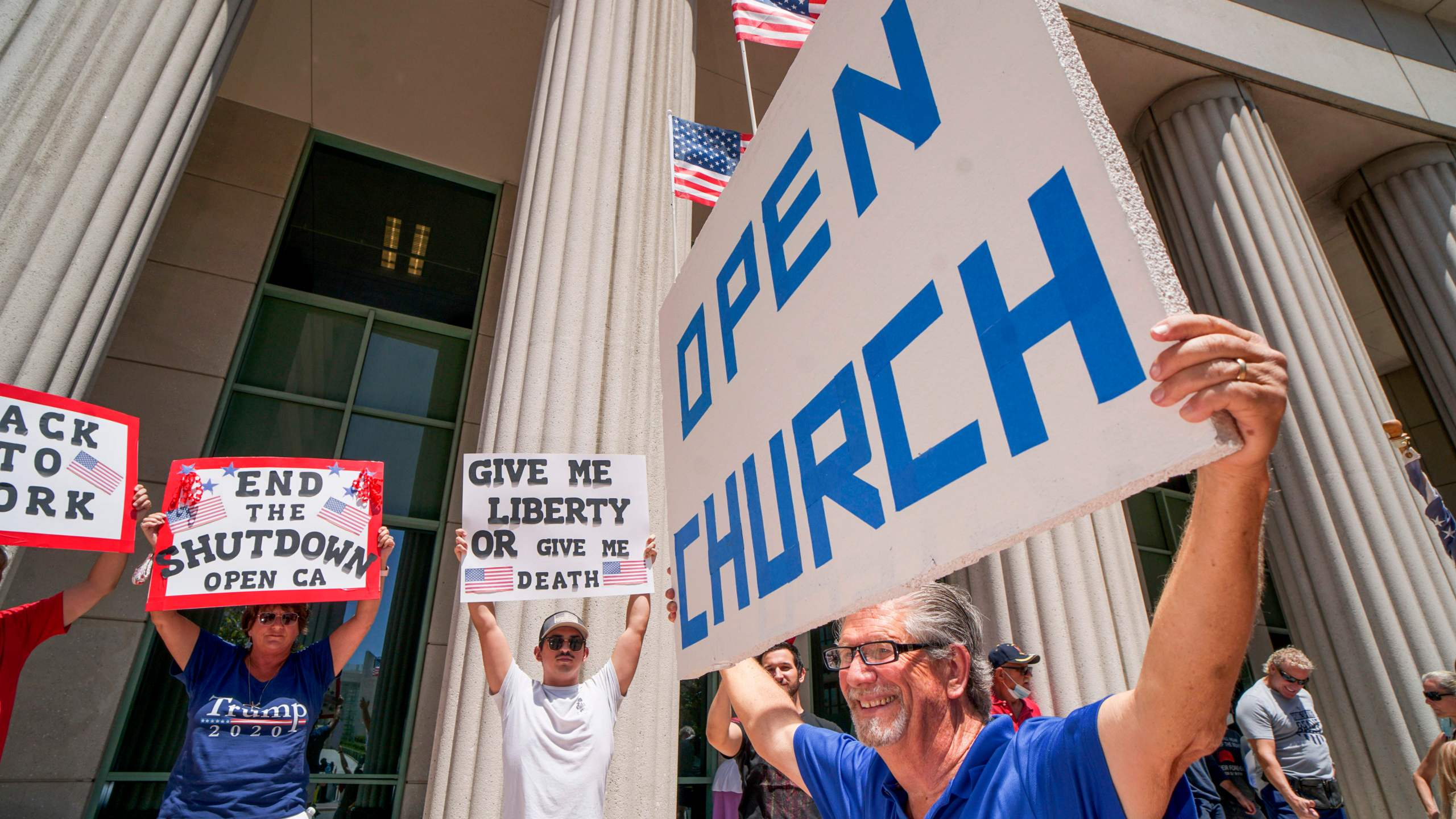 Demonstrators hold signs demanding their church to reopen during a rally against stay-home orders in San Diego on May 1, 2020. (Sandy Huffaker / AFP / Getty Images)