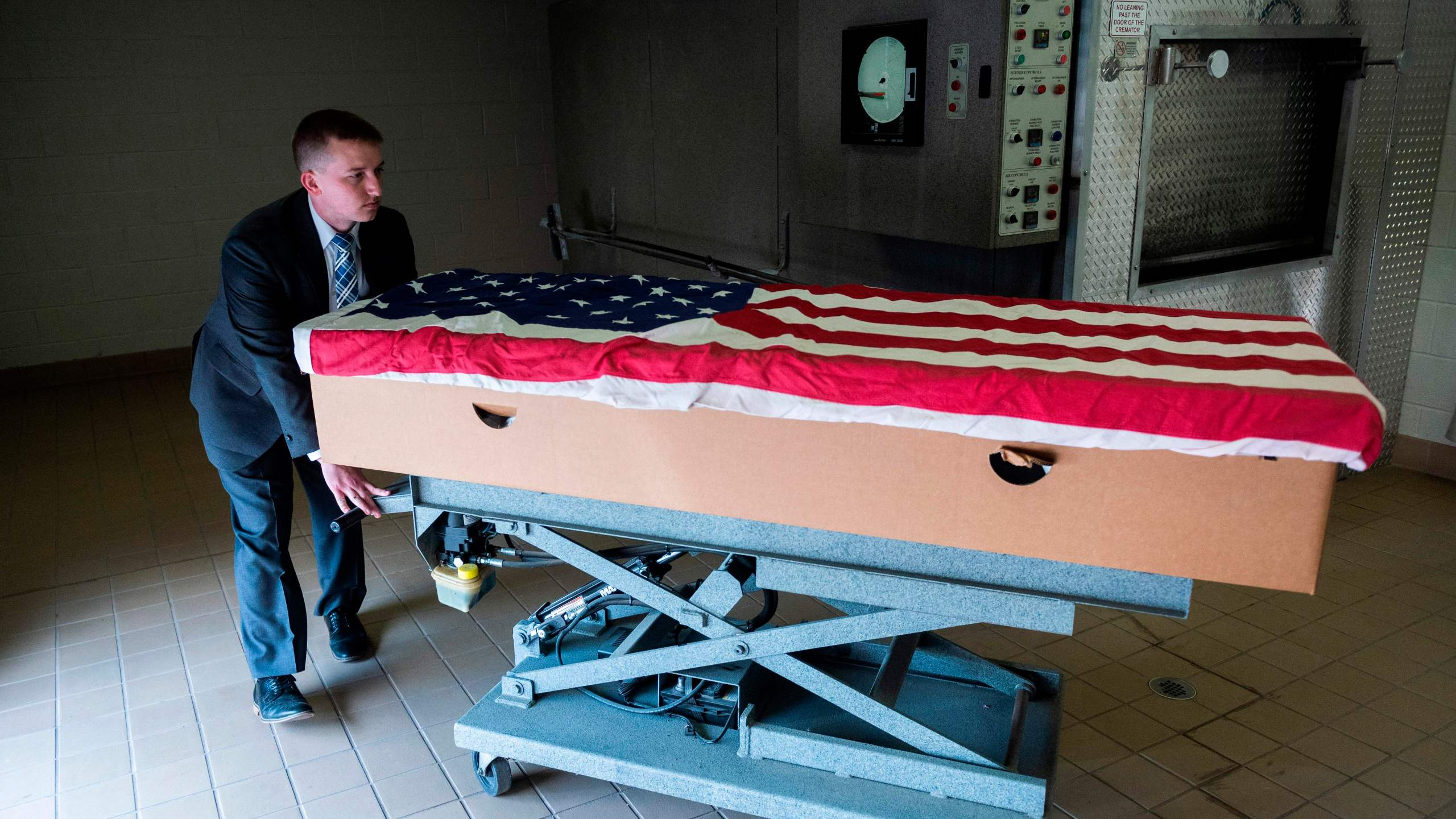 Crematory operator Brandon Cochran pushes a cremation box draped in a U.S. national flag, containing the body a veteran who died of COVID-19, to an incinerator at the Stauffer Funeral Homes in Frederick, Maryland on May 1, 2020. (ANDREW CABALLERO-REYNOLDS/AFP via Getty Images)