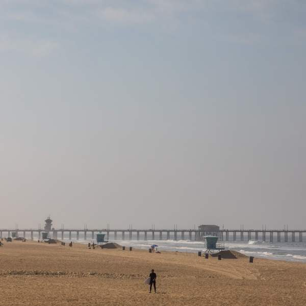 A surfer walks in a empty beach in Huntington Beach on May 2, 2020. (APU GOMES/AFP via Getty Images)