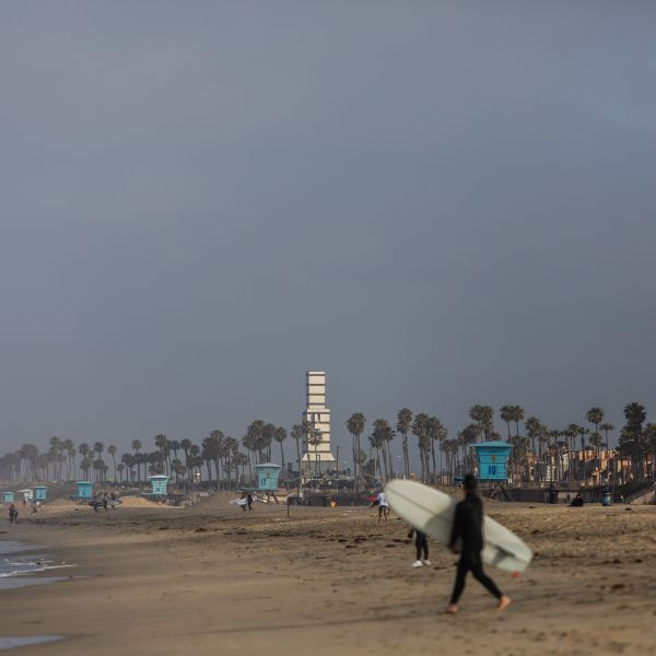 A surfer walks on the beach in Huntington Beach on May 2, 2020. (APU GOMES/AFP via Getty Images)