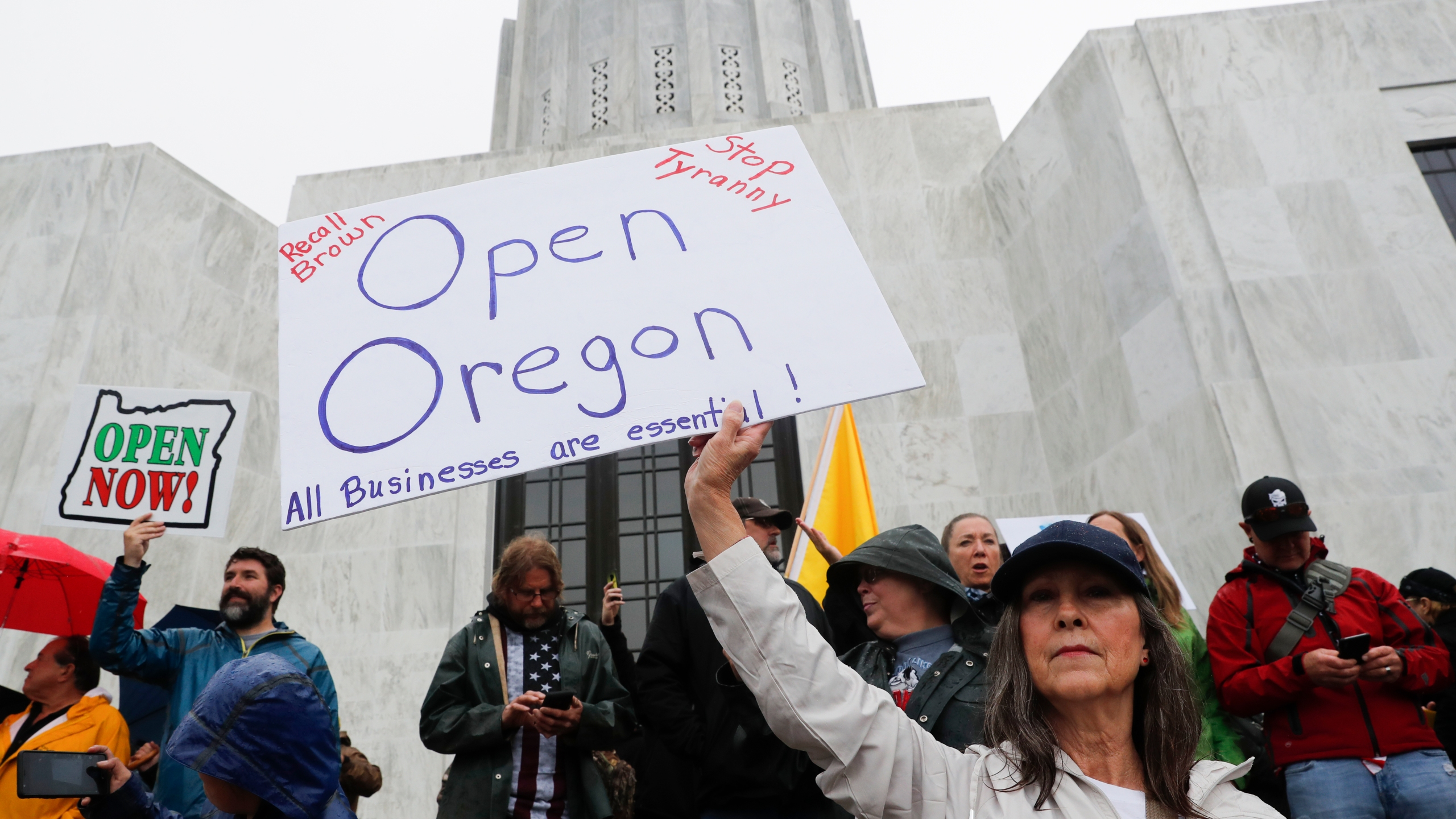 A woman holds a sign saying on the steps of the state capitol at the ReOpen Oregon Rally on May 2, 2020 in Salem, Oregon. (Terray Sylvester/Getty Images)