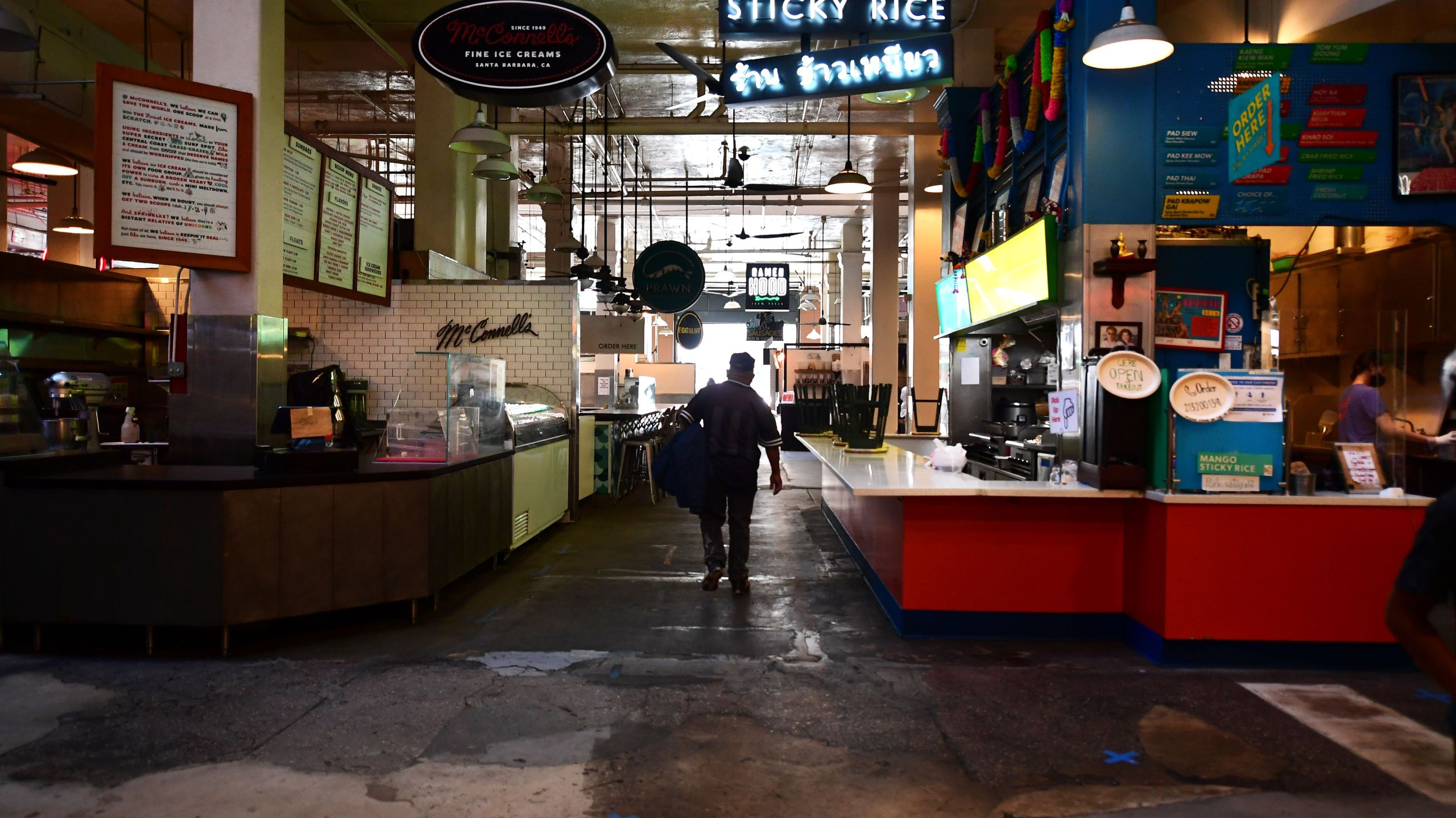 Some restaurants close as other remain open for takeout, observing new social distancing rules, with blue tape marked on the floor, at what would normally be a crowded lunctime scene at the Grand Central Market in Los Angeles, California on May 4, 2020. (FREDERIC J. BROWN/AFP via Getty Images)