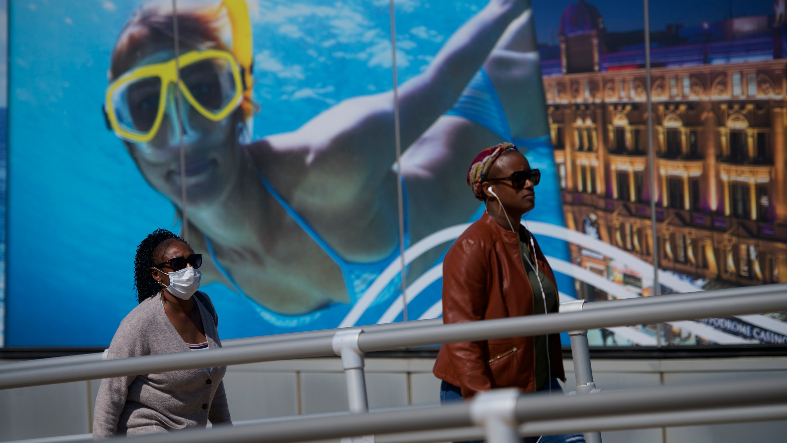 A pedestrian wears a mask while walking past a casino scuba diving poster during the coronavirus pandemic on May 7, 2020, in Atlantic City, New Jersey. (Mark Makela/Getty Images)