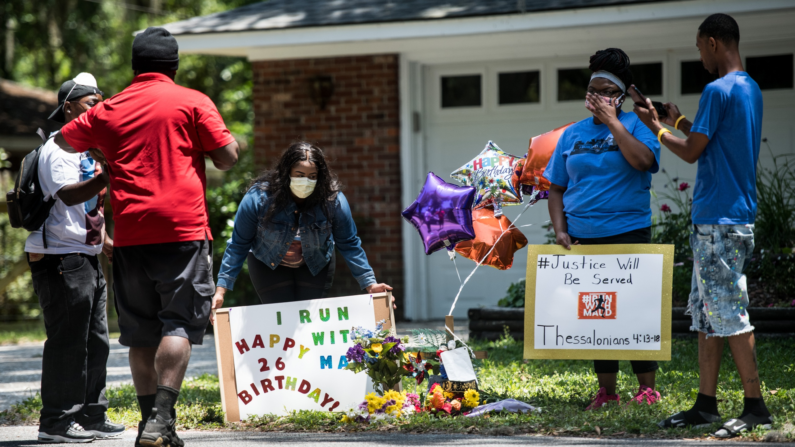 Demonstrators hold signs at a memorial for Ahmaud Arbery on May 8, 2020, near where he was shot and killed in Brunswick, Georgia. (Credit: Sean Rayford / Getty Images)