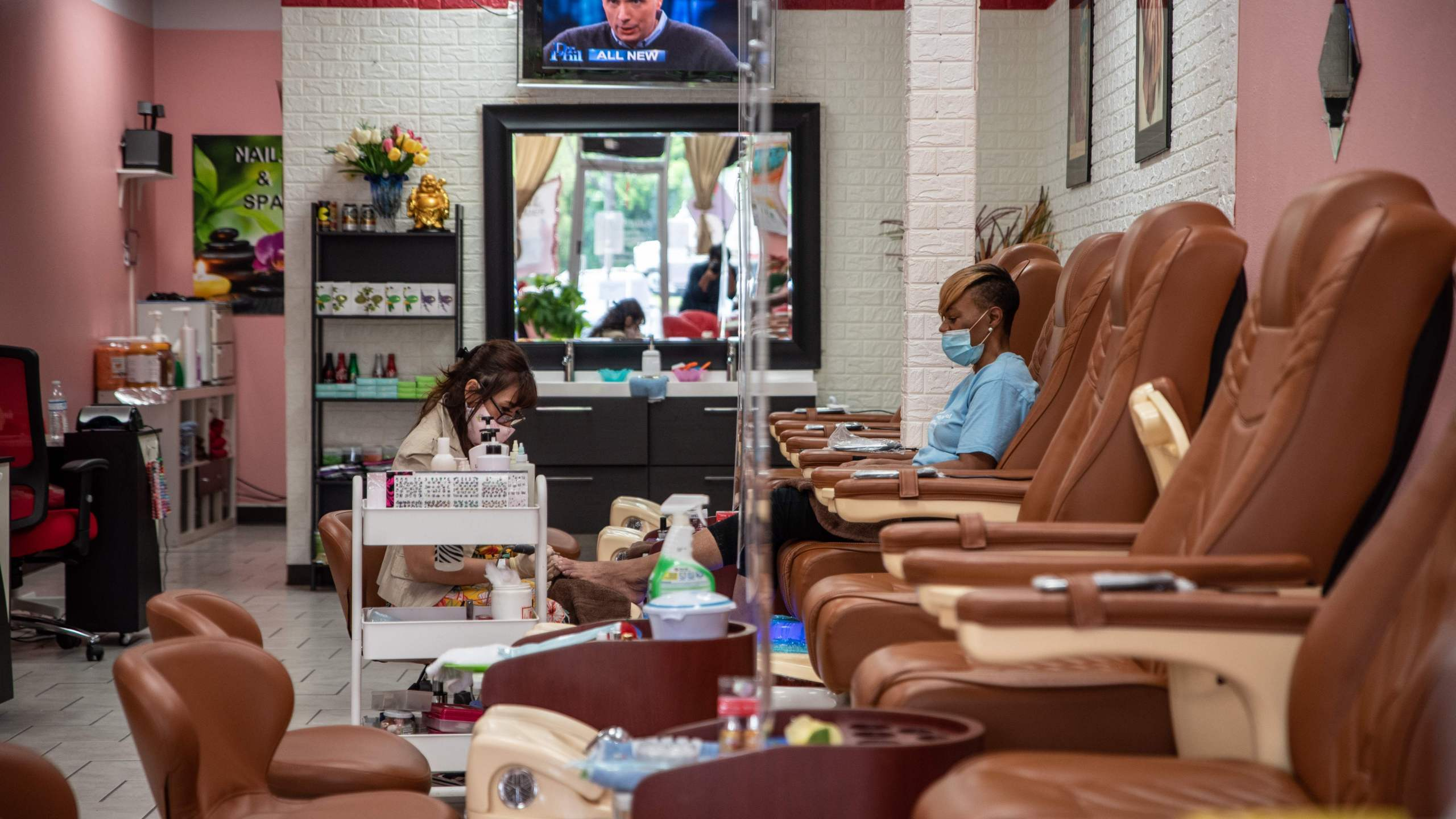A worker paints a woman's nails at a nail salon amid the coronavirus pandemic in Austin, Texas, on May 8, 2020, following a slow reopening of the economy. (Sergio Flores / AFP / Getty Images)