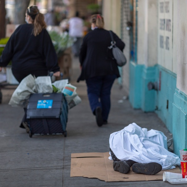 People carrying flowers pass by a homeless person sleeping on the sidewalk in downtown Los Angeles on May 8, 2020. (David McNew/Getty Images)