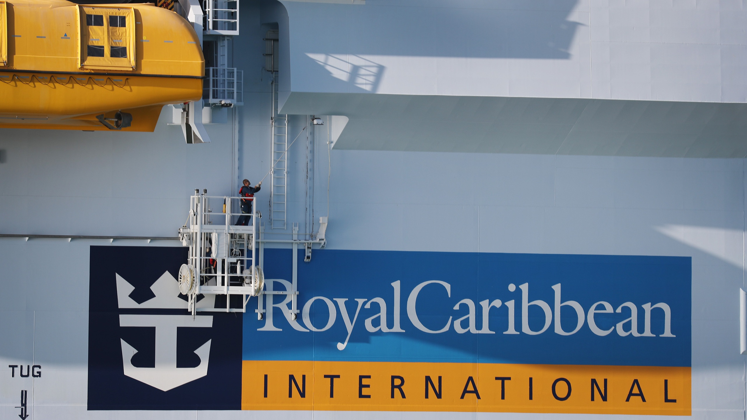 A worker paints the side of the Royal Caribbean Symphony of the Seas cruise ship, which is the world's largest passenger liner, as it is docked at Port Miami after returning to port from a Eastern Caribbean cruise as the world grapples with the coronavirus outbreak on March 14, 2020 in Miami, Florida. (Joe Raedle/Getty Images)