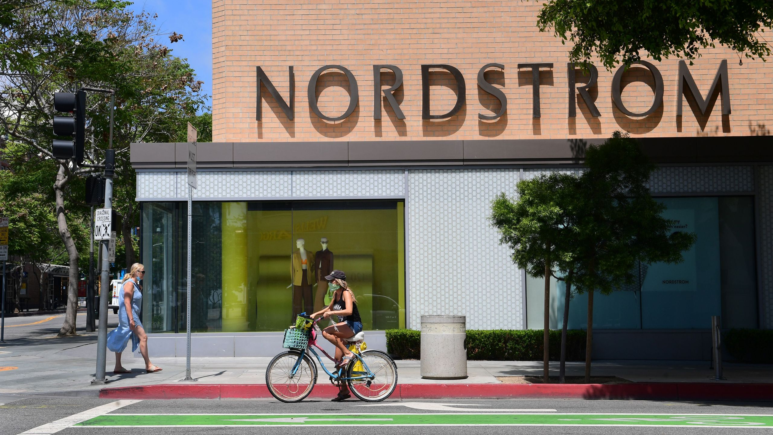 A pedestrian and cyclist wear face masks outside a branch of department store chain Nordstrom in Santa Monica on May 11, 2020. (FREDERIC J. BROWN/AFP via Getty Images)