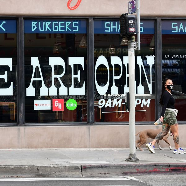Pedestrians wear face masks in front of a restaurant in Los Angeles on May 12, 2020. (Frederic J. Brown / AFP / Getty Images)