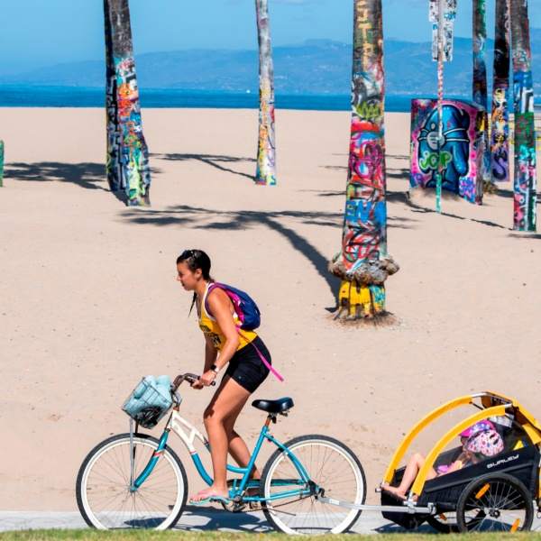 A person bikes on a closed path at Venice Beach on May 13, 2020. (VALERIE MACON/AFP via Getty Images)