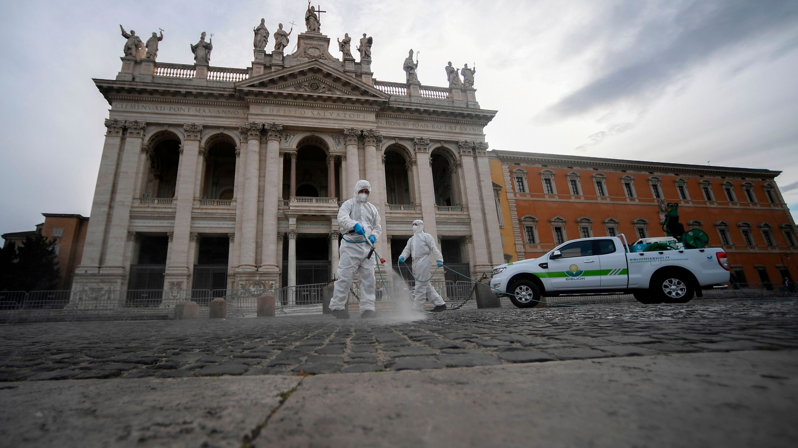 Employees of a disinfecting services company, wearing protective overalls and mask, spray sanitizer at the Archbasilica of Saint John Lateran (San Giovanni in Laterano) in Rome on May 15, 2020. (FILIPPO MONTEFORTE/AFP via Getty Images)