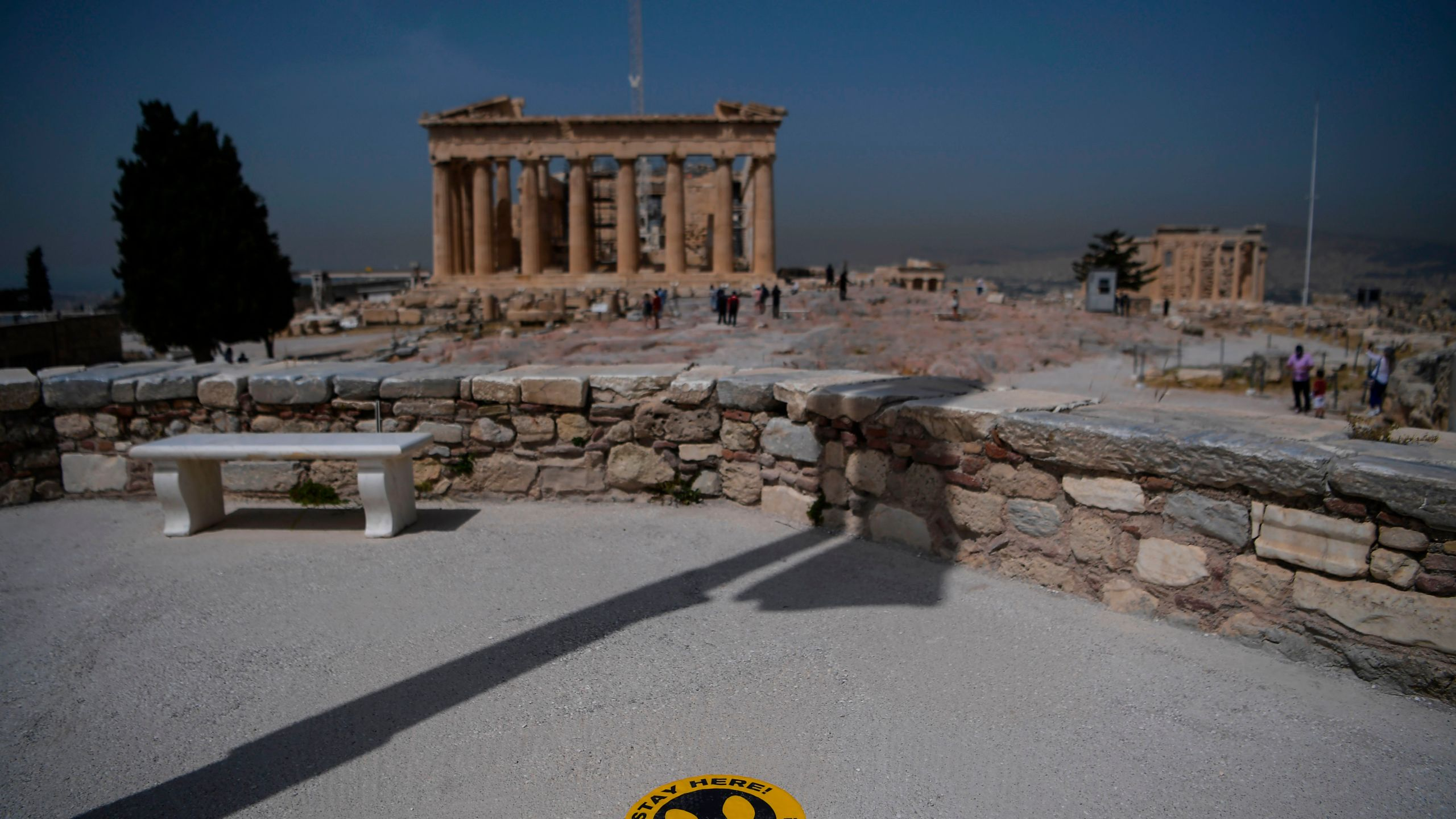 A picture taken on May 18, 2020 shows a sticker marking social distance on the ground in front of the Parthenon temple on the archeological site of the Acropolis in Athens amid the pandemic of the novel coronavirus. (Aris MESSINIS / Getty Images via AFP)