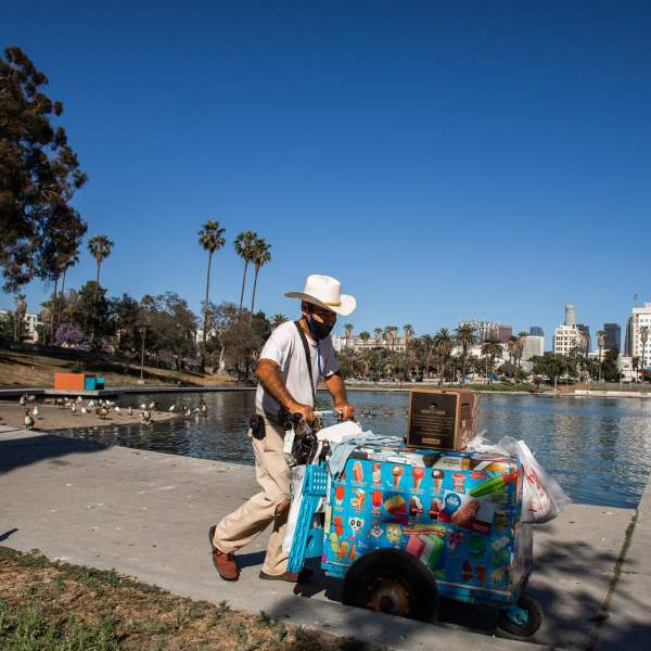 A ice-cream street vendor pushes his cart in MacArthur Park, Los Angeles on May 21, 2020. (APU GOMES/AFP via Getty Images)