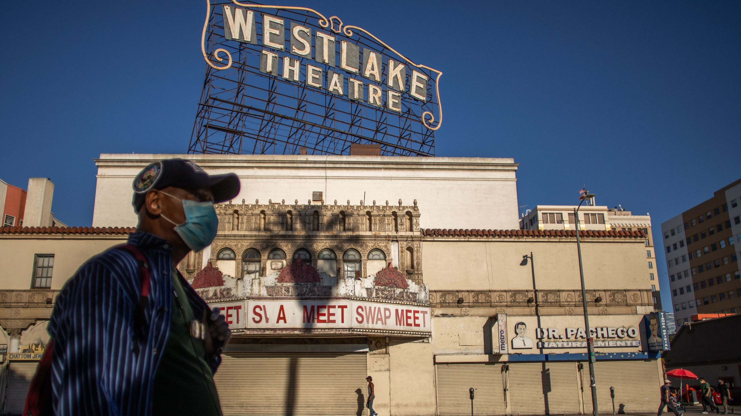 A man wearing a facemask walks in front of a closed store in the Westlake area by MacArthur Park, Los Angeles on May 21, 2020. (APU GOMES/AFP via Getty Images)