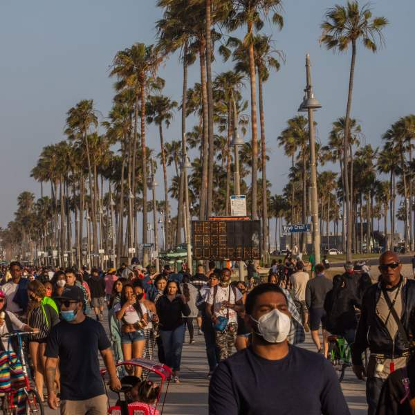 People walk at the boardwalk in Venice Beach during the first day of the Memorial Day holiday weekend amid the COVID-19, pandemic on May 23, 2020. (APU GOMES/AFP via Getty Images)