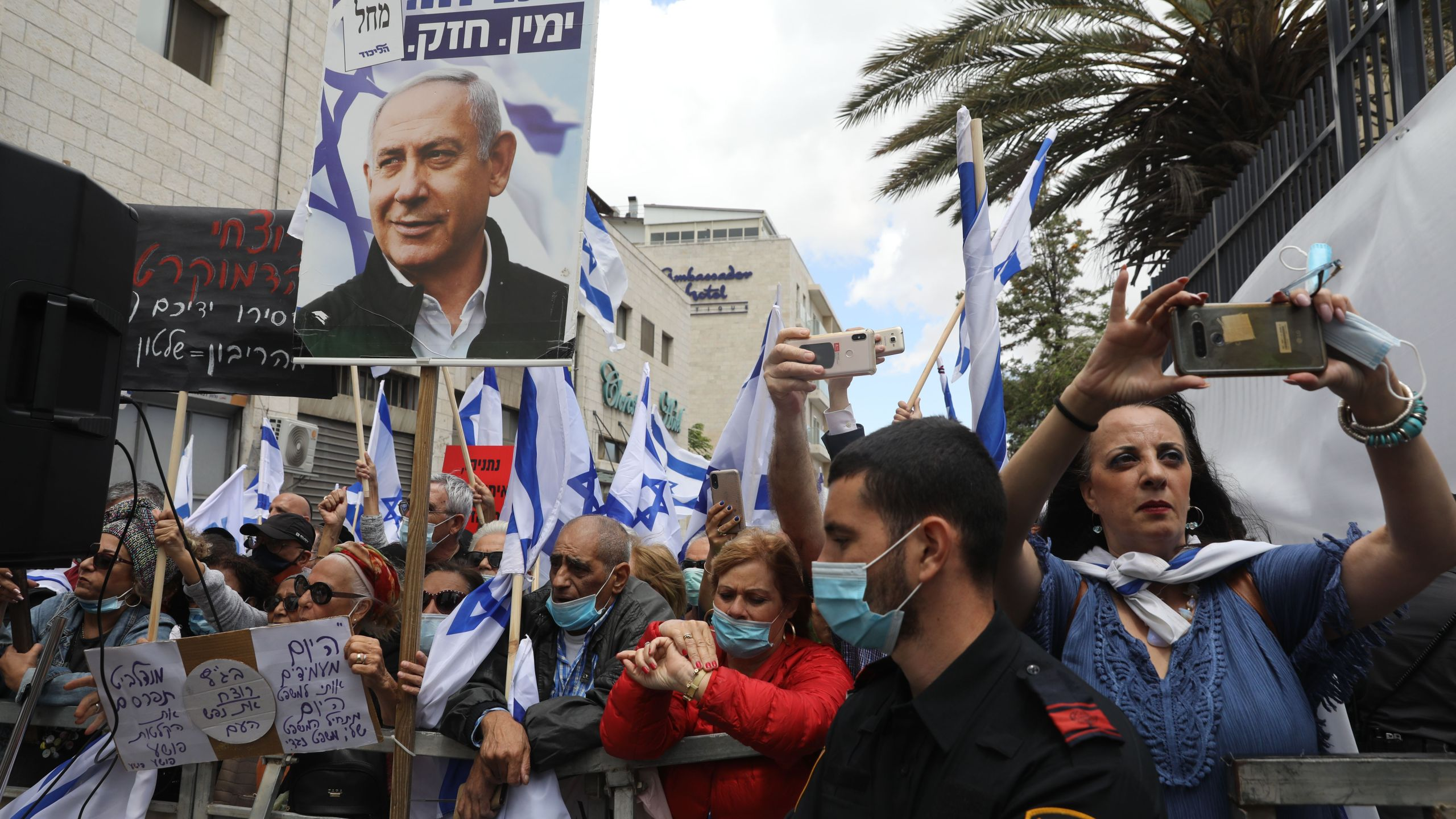 Israeli supporters hold flags and placards during a rally in support of Prime Minister Benjamin Netanyahu outside the district court of Jerusalem on May 24, 2020. (MENAHEM KAHANA/AFP via Getty Images)