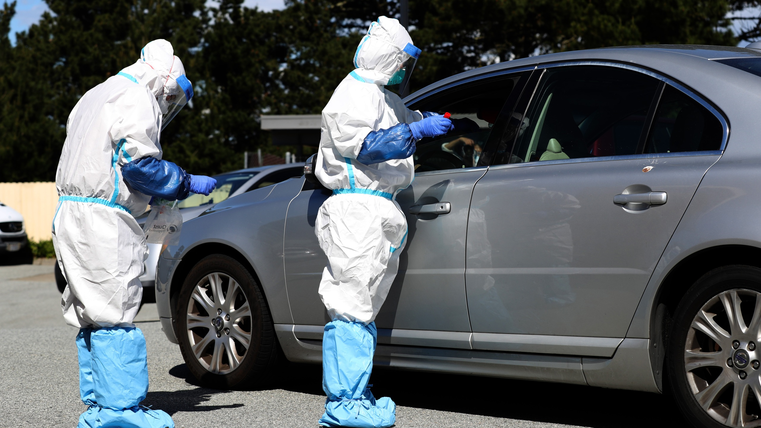 Medical professionals administer a coronavirus test during a drive-thru testing station on March 26, 2020 in Daly City. (Justin Sullivan/Getty Images)