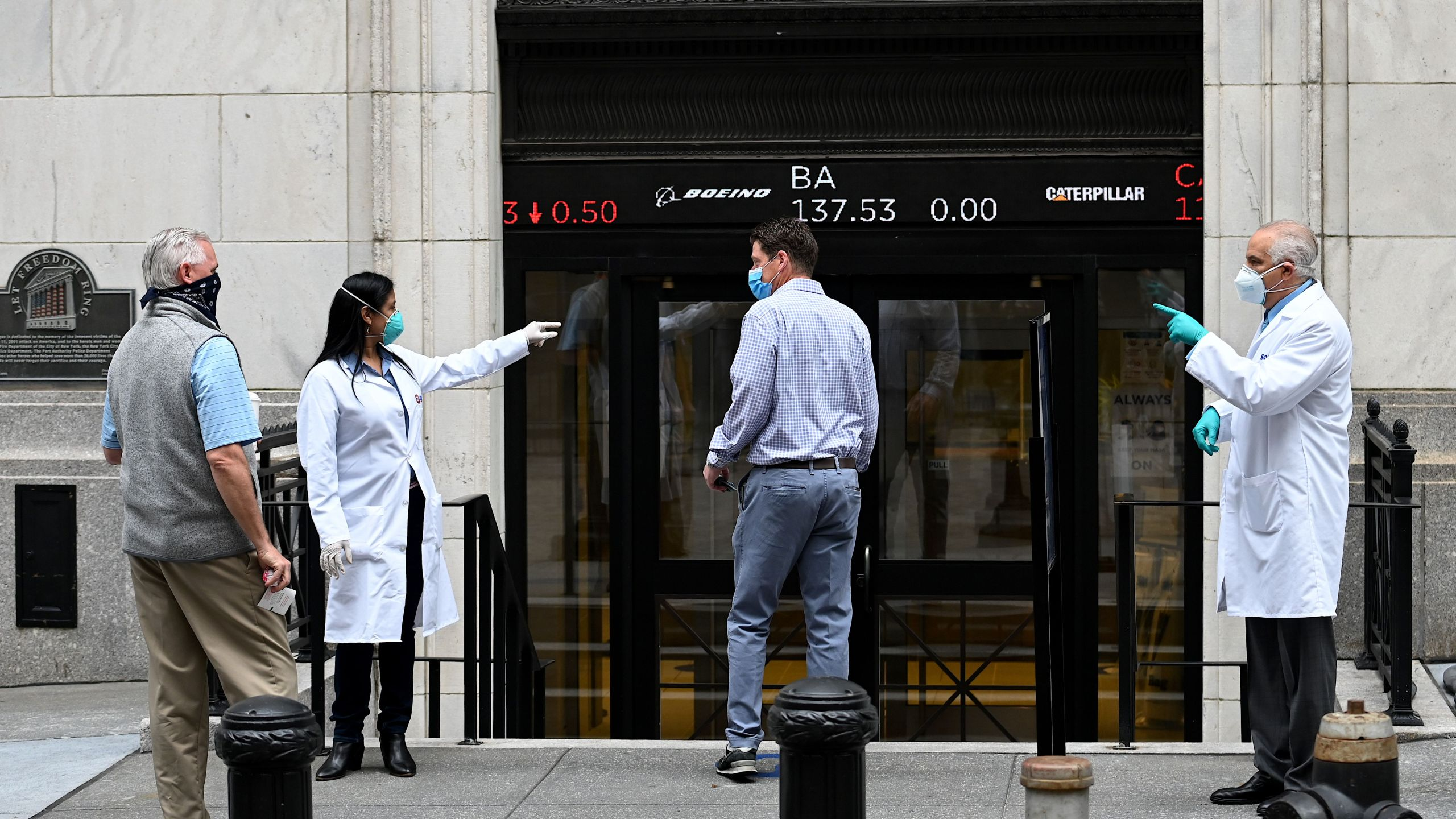 Medical workers check traders wearing masks as they arrive before the opening bell at the New York Stock Exchange on May 26, 2020 at Wall Street in New York City. (JOHANNES EISELE/AFP via Getty Images)
