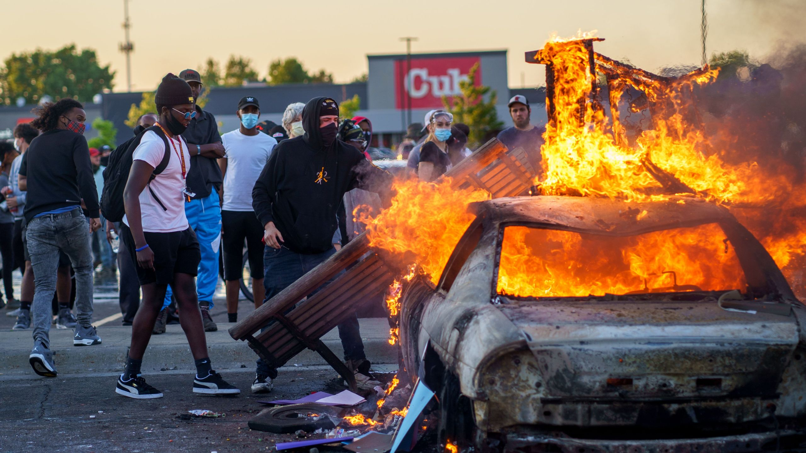 Protesters throw objects onto a burning car outside a Target store near the Third Police Precinct in Minneapolis, Minnesota, on May 28, 2020, during a demonstration over the death of George Floyd. (Kerem Yucel / AFP / Getty Images)