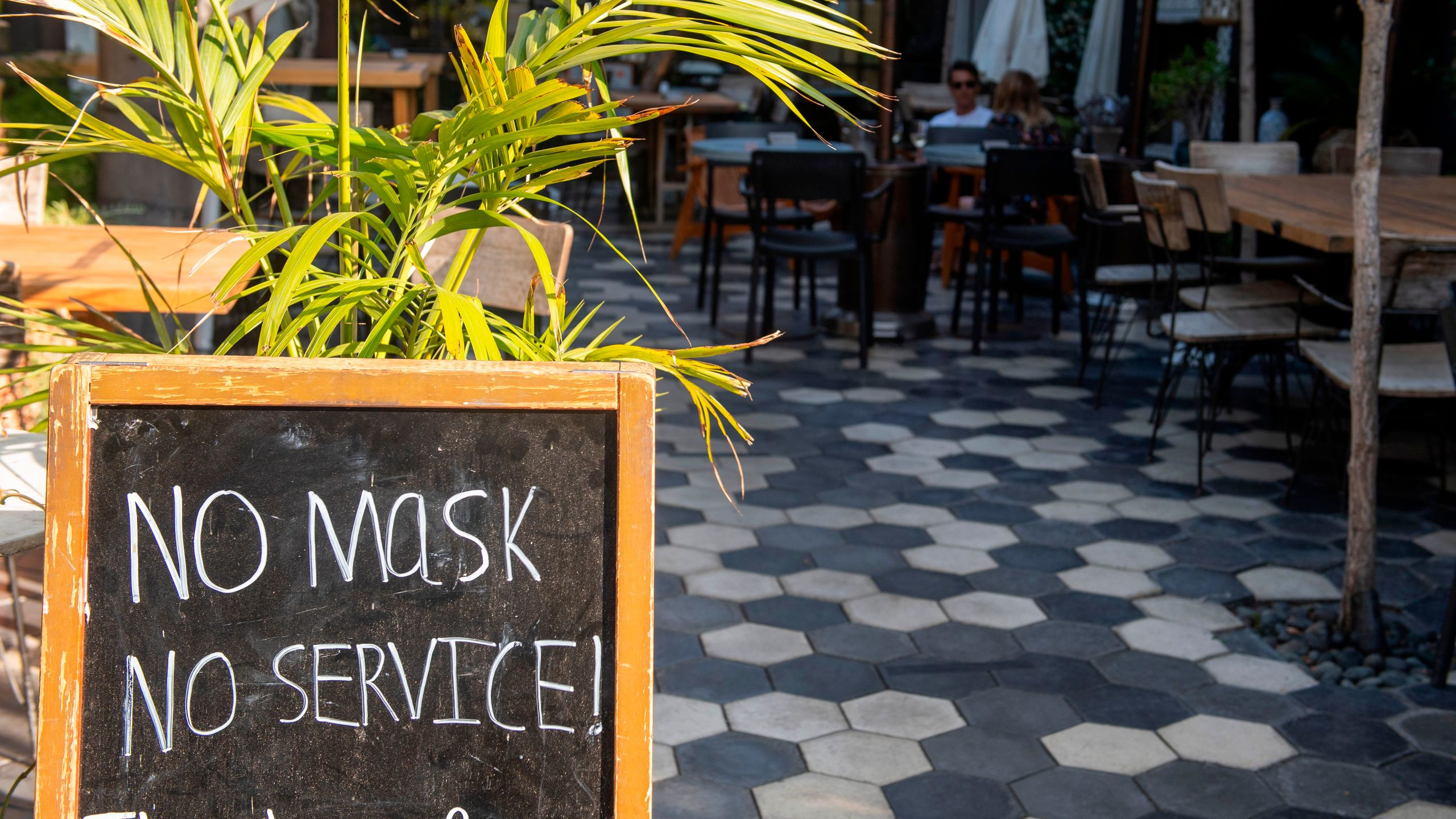 "A sign at a restaurant in West Hollywood reads ""no mask, no service"" on May 29, 2020. (VALERIE MACON/AFP via Getty Images)"