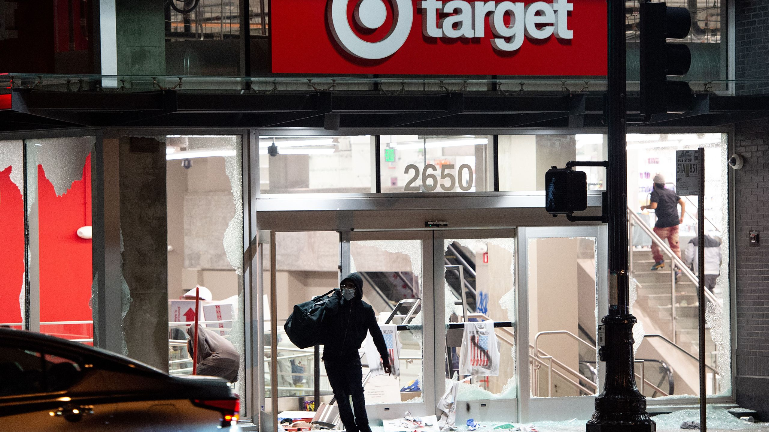 A looter steals items from a Target store as protesters face off with police in Oakland, Calif. on May 30, 2020. Protesters are rallying against police brutality nationwide following the death of George Floyd, a black man who died after a white policeman kneeled on his neck for several minutes. (JOSH EDELSON/AFP via Getty Images)