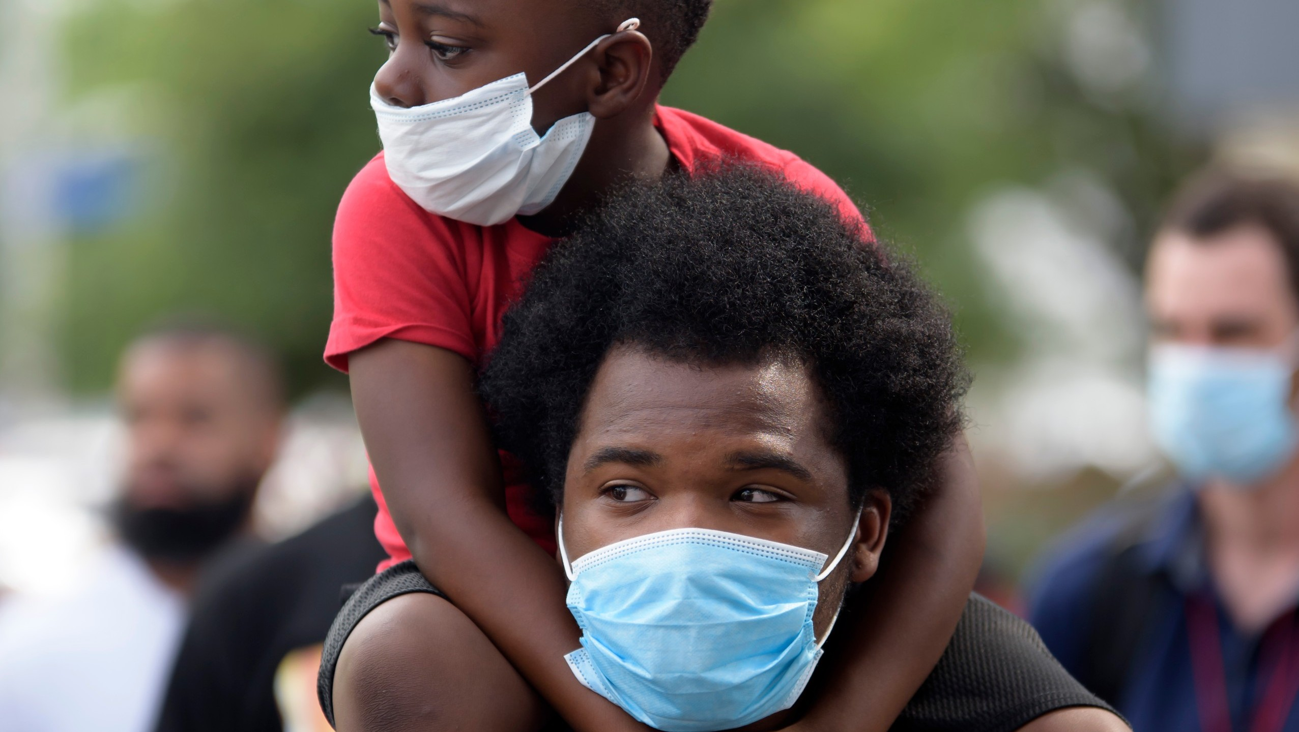 "A young boy sits on the shoulder's of a man, both wearing facemasks, during a ""Justice for George Floyd"" event in Houston, Texas on May 30, 2020, after George Floyd, an unarmed black, died while being arrested and pinned to the ground by a Minneapolis police officer. (MARK FELIX/AFP via Getty Images)"