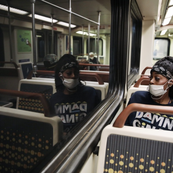 A woman wears a face mask while riding a Los Angeles Metro Rail train amid the coronavirus pandemic on April 1, 2020, in Los Angeles. (Mario Tama/Getty Images)