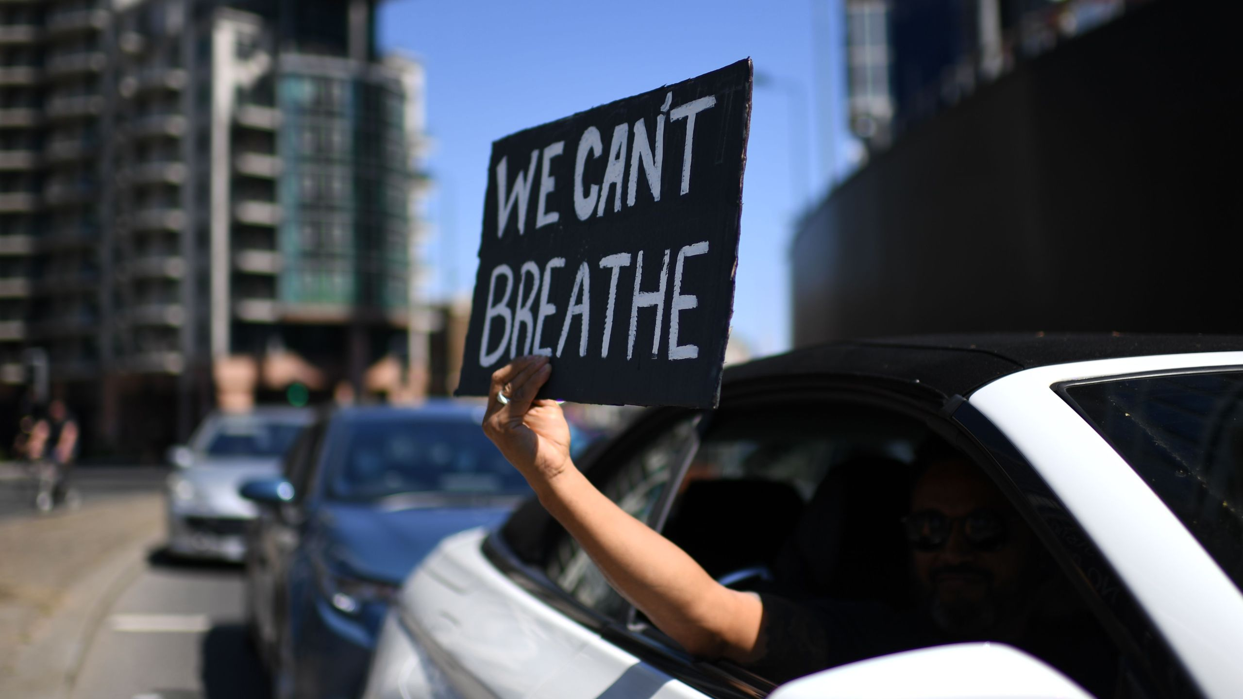 "A sign displaying the message ""We Can't Breathe"" is held out of a car window as demonstrators make their way towards the U.S. Embassy in central London on May 31, 2020, to protest the death of George Floyd, who died after a police officer knelt on his neck for nearly nine minutes during an arrest in Minneapolis. (DANIEL LEAL-OLIVAS/AFP via Getty Images)"