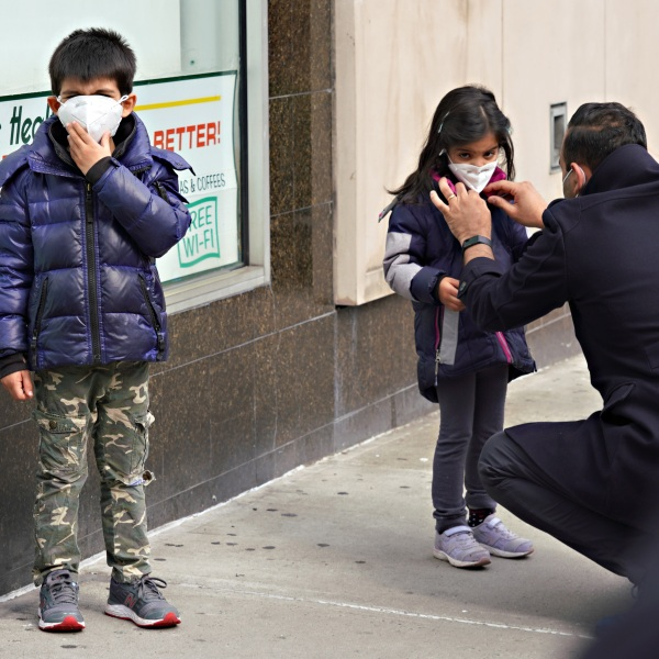 A man adjusts a child's protective mask amid the coronavirus pandemic on April 5, 2020 in New York City. (Cindy Ord/Getty Images)