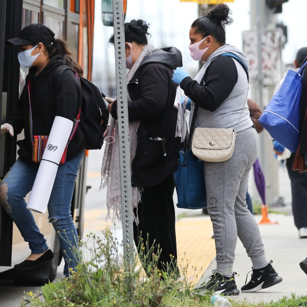 People board a bus wearing face masks amid the coronavirus pandemic on April 6, 2020 in South Los Angeles. (Mario Tama/Getty Images)