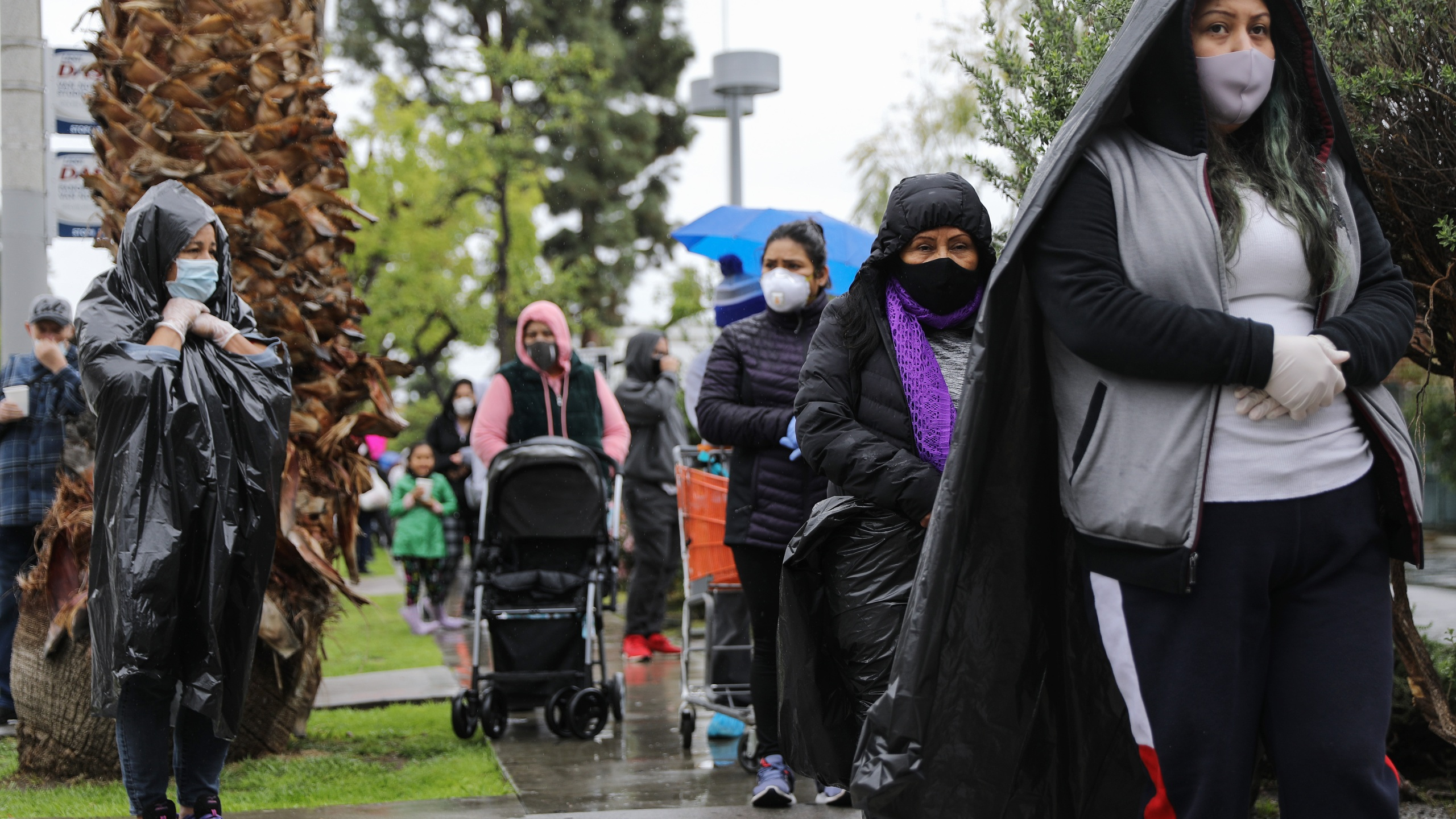 Juana Gomez, 50, from North Hollywood, wears a face mask and gloves, while using a trash bag to protect against the rain, as she waits in line to receive food at a Food Bank distribution for those in need as the coronavirus pandemic continues on April 9, 2020, in Van Nuys, Calif. (Mario Tama/Getty Images)