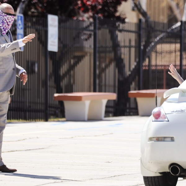 Pastor Jerel Hagerman (L) waves to a departing congregant after conducting a drive-in 'car church' Easter service in the parking lot of Joshua Springs Calvary Chapel amidst the coronavirus pandemic on April 12, 2020 in Yucca Valley, California. (Mario Tama/Getty Images)