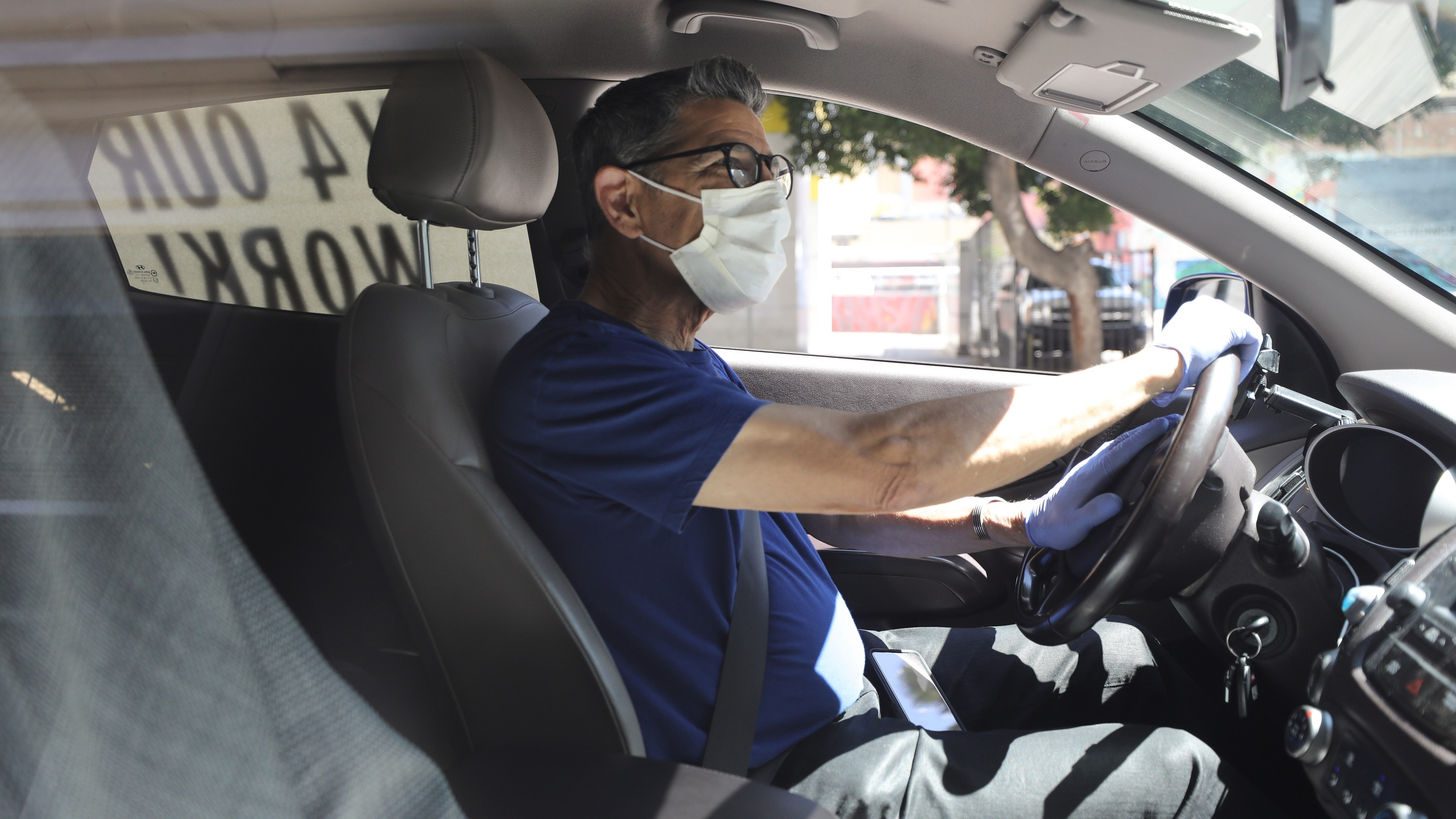 """A driver wears a face mask and gloves as Uber and Lyft drivers with Rideshare Drivers United and the Transport Workers Union of America conduct a """"caravan protest"""" outside the California Labor Commissioner's office in Los Angeles amid the coronavirus pandemic on April 16, 2020. (Mario Tama/Getty Images)"""