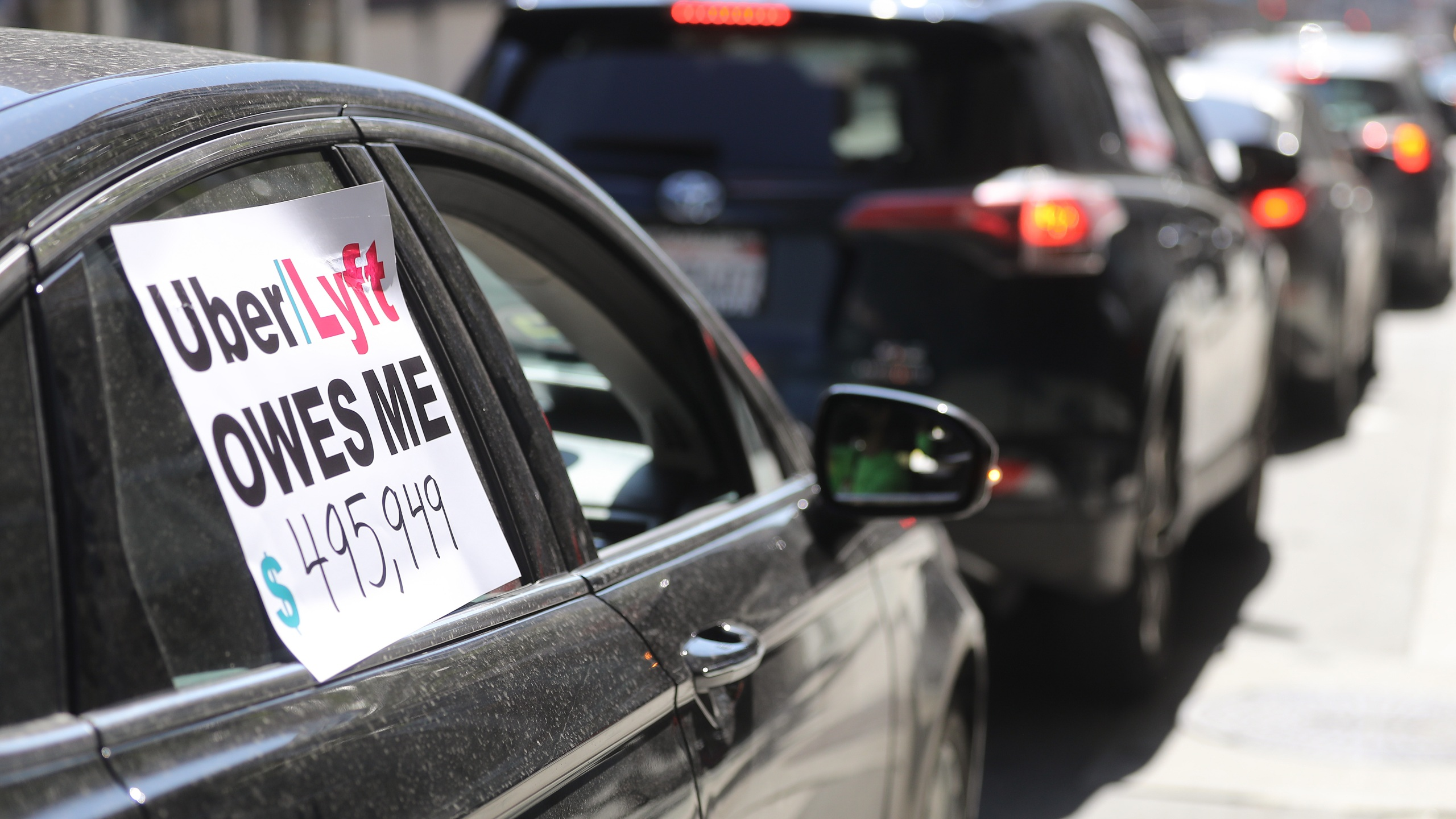 """Uber and Lyft drivers with Rideshare Drivers United and the Transport Workers Union of America conduct a """"caravan protest"""" outside the California Labor Commissioner's office amidst the coronavirus pandemic on April 16, 2020 in Los Angeles. (Mario Tama/Getty Images)"""