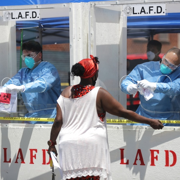 Women are tested for COVID-19 by members of the Los Angeles Fire Department wearing personal protective equipment in Skid Row amidst the coronavirus pandemic on April 21, 2020 in Los Angeles, California. Health officials reported that 43 people tested positive for COVID-19 at one Skid Row homeless shelter. (Mario Tama/Getty Images)