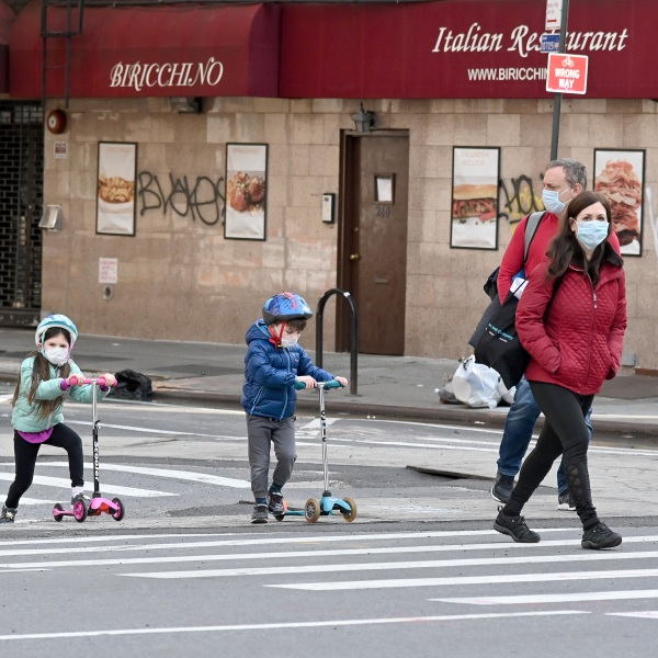 Children wearing face masks play on their scooters while their parents watch during the coronavirus pandemic on April 25, 2020 in New York City. (Jamie McCarthy/Getty Images)