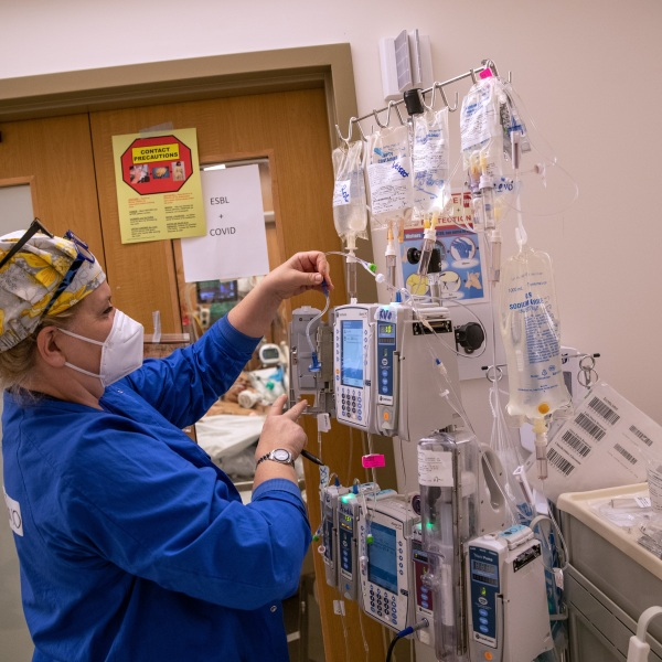 A nurse wearing an N95 mask adjusts IV equipment hanging outside a COVID-19 patient's door in a Stamford Hospital intensive care unit (ICU), on April 24, 2020, in Stamford, Conn. (John Moore/Getty Images)