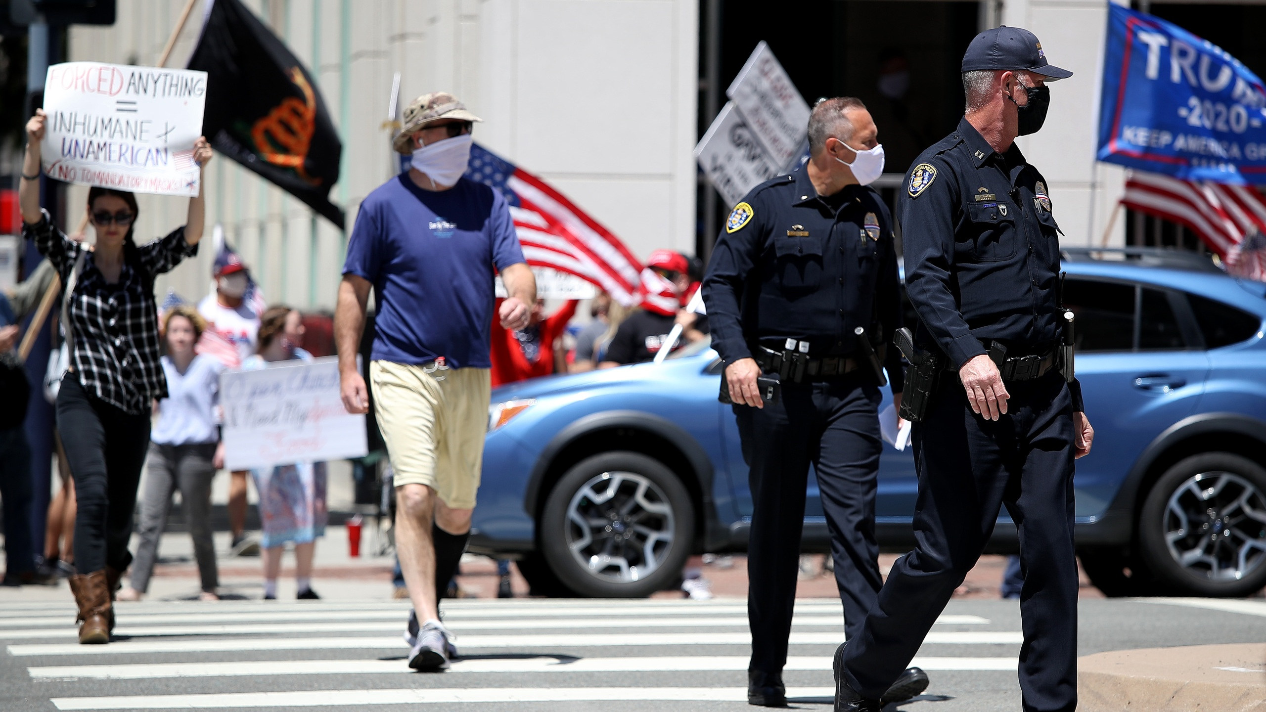 San Diego Police Department officers look on as activists hold signs and protest the California lockdown due to the coronavirus pandemic on May 1, 2020, in San Diego. (Sean M. Haffey/Getty Images)