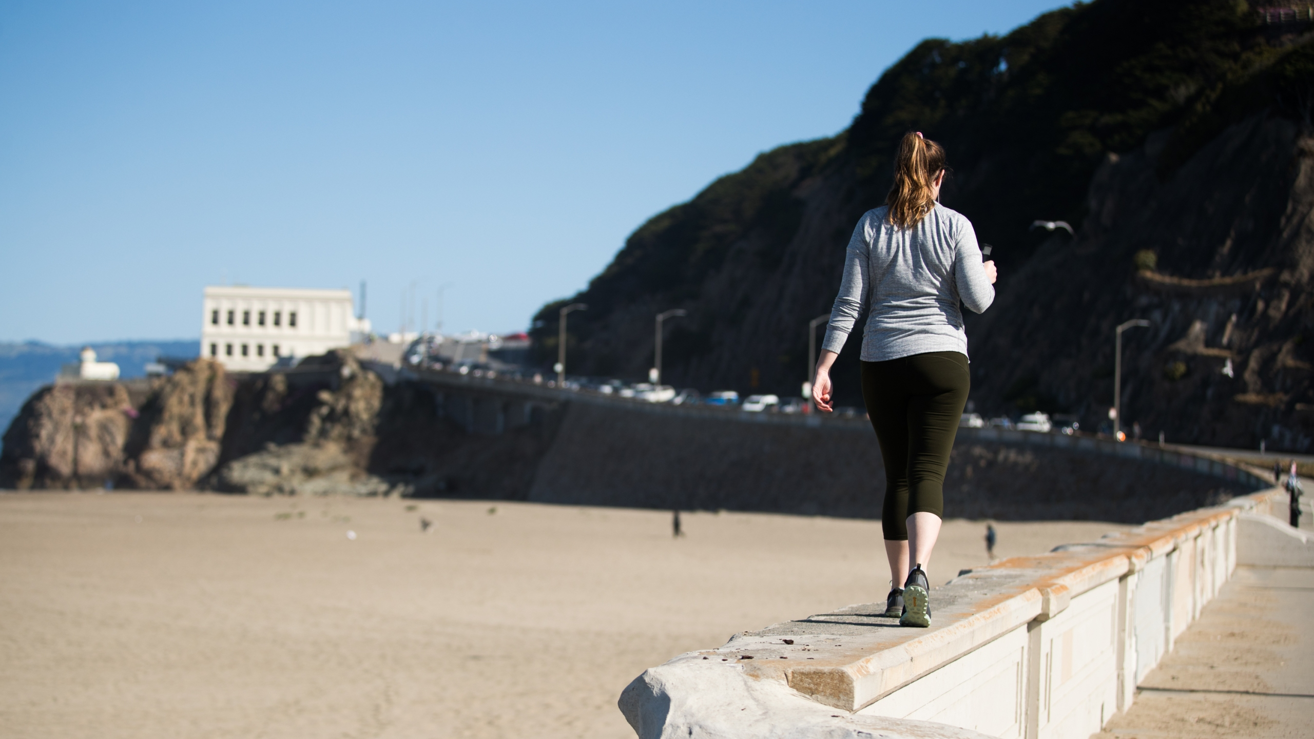 A woman walks on a beach path during the coronavirus pandemic on May 3, 2020 in San Francisco. (Rich Fury/Getty Images)
