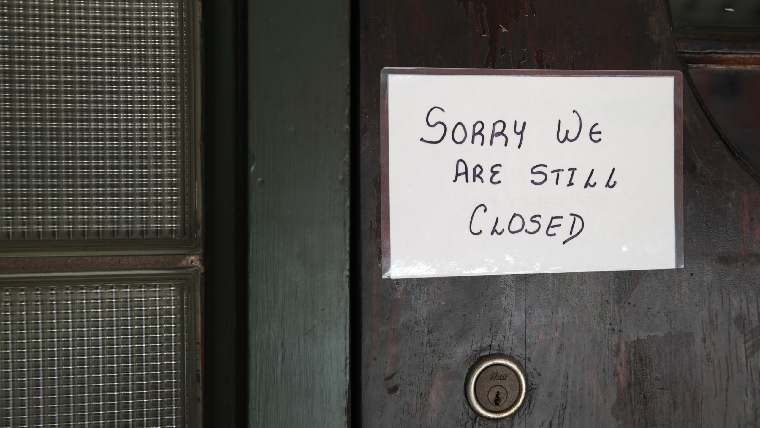 A sign on the door of Flannery's Tavern lets customers know the business is still closed on May 13, 2020 in Chesterton, Indiana. (Scott Olson/Getty Images)